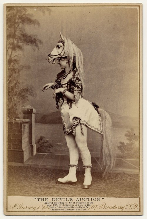 1867. Eliza Blasina wearing horse-head headdress, short costume with attached horsetail, rows of round beads or bells around ankles, wrists, neck and upper arm.